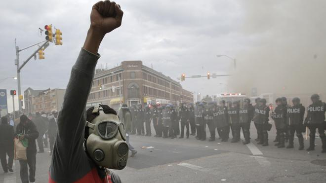 A demonstrator raises his fist as police stand in formation as a store burns, Monday, April 27, 2015, during unrest following the funeral of Freddie Gray in Baltimore. Gray died from spinal injuries about a week after he was arrested and transported in a Baltimore Police Department van. (AP Photo/Patrick Semansky)